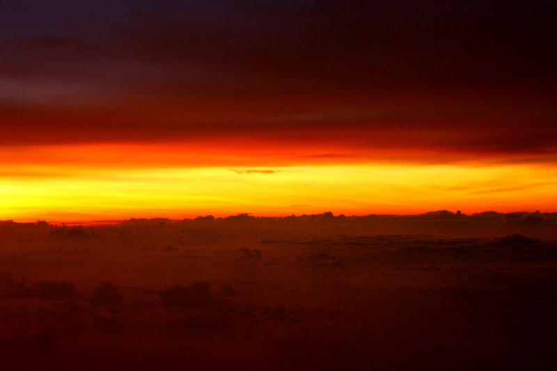 A cloudy sunset with a bright streak of yellow and two narrow streaks of red merging with black on either side