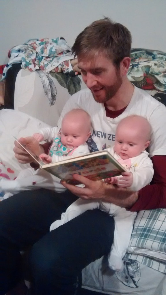 Father with twins reading
