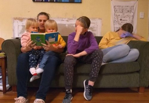 Twin girls on woman's lap reading book with teenagers on sofa
