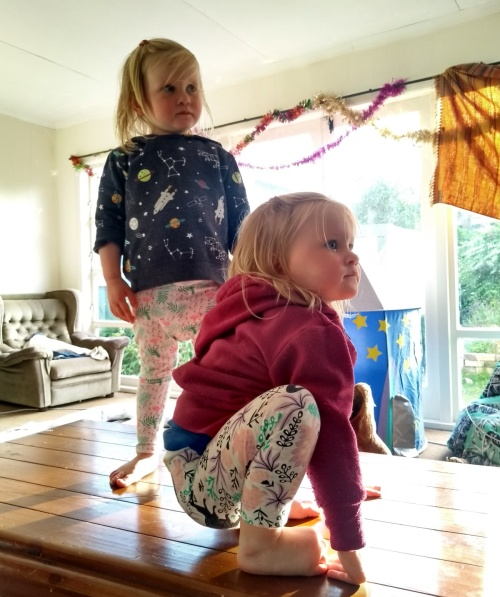 Children standing on table in sunny room watching looking to right