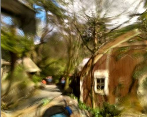 Warped view of old buildings and trees through thick glass window