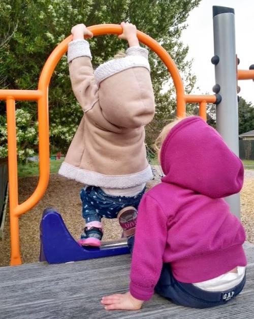 Children in hoodies playing on playground platform above slide