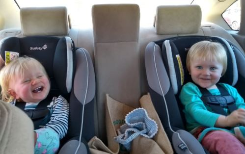 Young children laughing in back of car