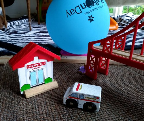 Toy hospital and ambulance on carpeted floor with balloon
