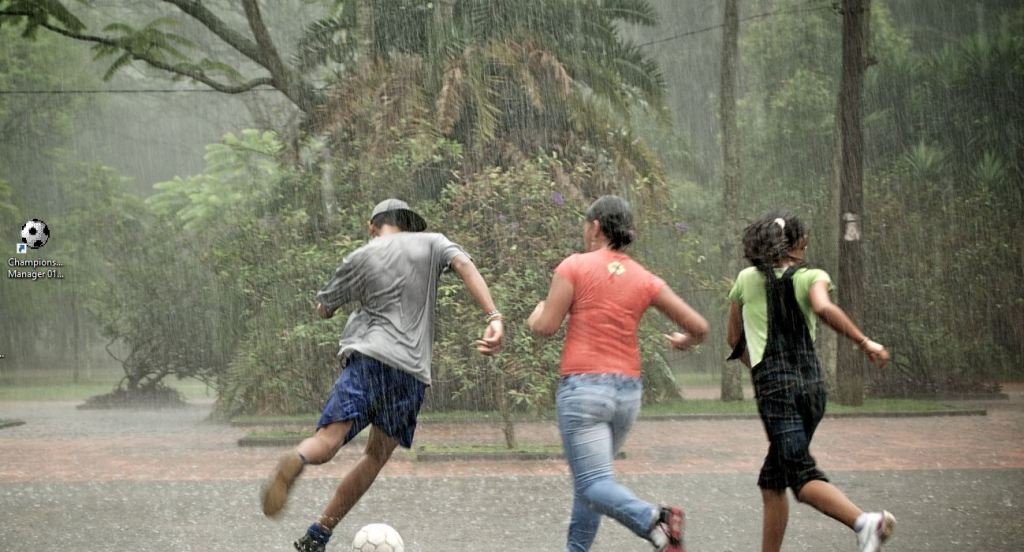 Teenagers playing football | soccer in the rain in Brazil with game icon on desktop